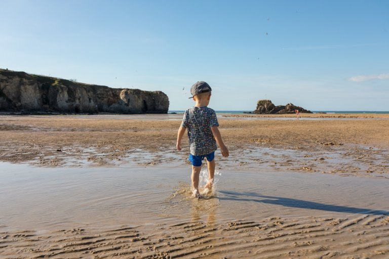 Child paddling on the beach in Perranporth